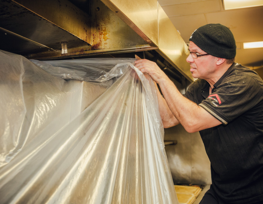 Man removing plastic cover from kitchen equipment